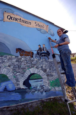 Artist Catherine Cronin works on her mural at The Quiet Man Stud