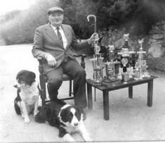 Christy Butler with Trial trophies and dogs