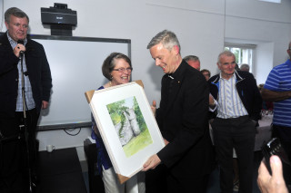Doc Gilbert presents one of her paintings to F'r Alan. | Tom Broderick