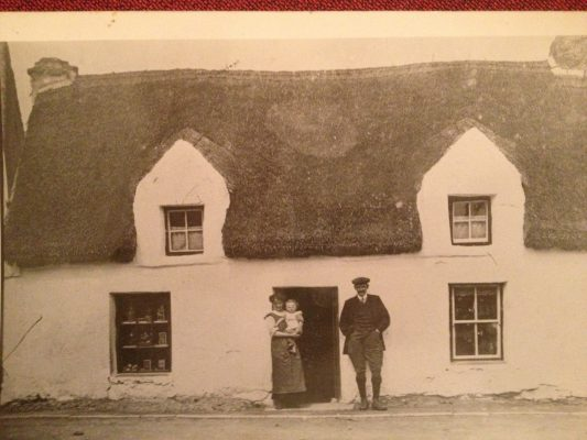 Ellen (Staunton) Faherty & child, man unknown. There were two house together in this property. One was known as 'The Burn House' – it seems it was burnt at some stage. The Faherty family lived here before they bought the property now known as Faherty's Pub across the Square. | Padraig Faherty