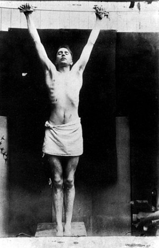 Harry Clarke posing in his studio, for a design of Christ