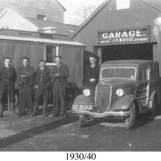 Circa 1930.  Moyst's Garage in Oughterard. R. to L. Jack Cleggett {Main Street} Michael John McDonagh {Clareville} & Jim Moyst {owner}. To the left, behind the caravan, can be seen Sullivan's Hall, now Supermacs Restaurant.