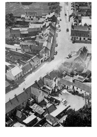 Aerial Photo of Oughterard (late 40s);Facing Houses on left; 1st is Tim Molloys (now Kennys); next is Monahan's Bicycle Shop (now a Hairdressers); then the house where Tom was born (now part of Henry Keoghs)